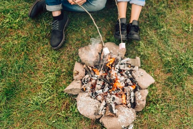 Beine eines paares in der nähe von feuer, die marshmallows rösten.