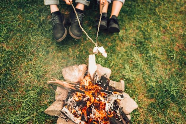 Beine eines paares in der nähe von feuer. picknickkonzept