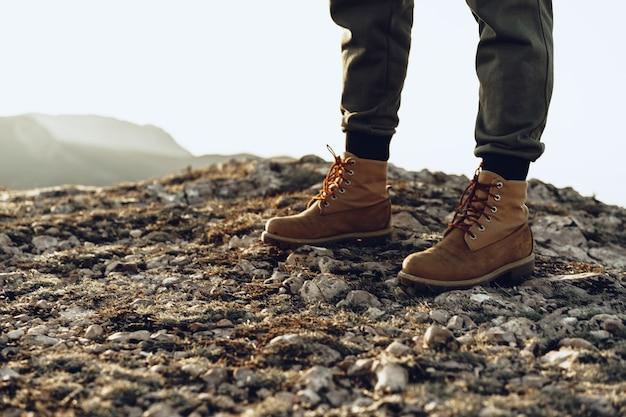 Beine eines rucksacktouristen in wanderschuhen, die auf der spitze des berges stehen