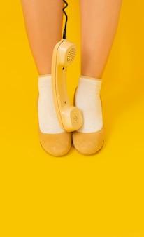 Beine gelber hintergrund retro mobilteil rohr empfänger schuhe lady vintage telefon 80er 90er jahre
