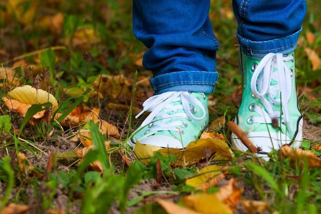 Beine in blue jeans und trendigen turnschuhen auf dem gras mit herbstblättern, konzept des urbanen looks für die alltägliche jugend