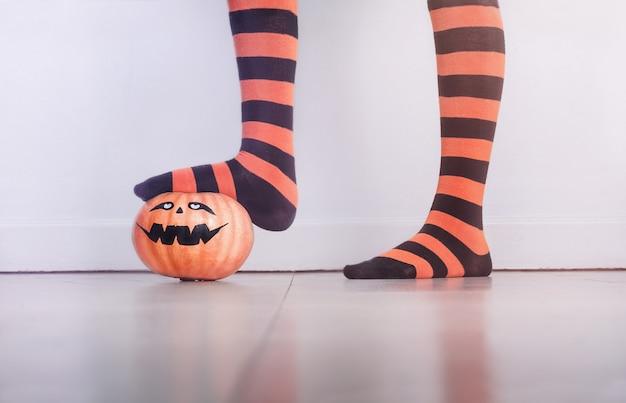 Beine in gestreiften strümpfen halten einen halloween-kürbis