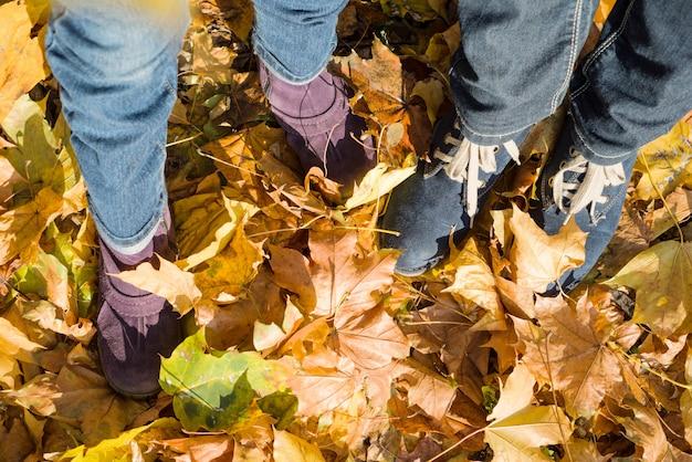 Beine in jeans und stiefeln von frau und kind auf gelben blättern