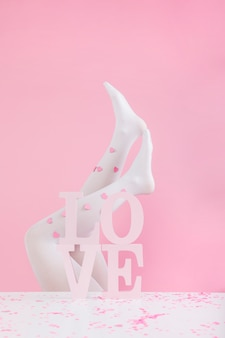 Beine in strumpfhosen mit papierherzen in der nähe von weißen liebesaufschrift