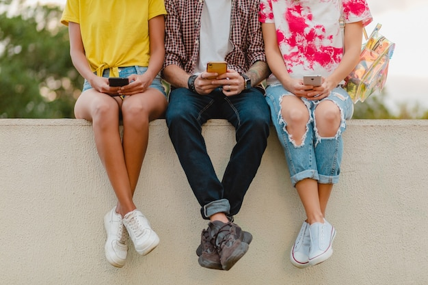 Beine in turnschuhen der jungen gesellschaft von freunden, die park mit smartphones sitzen