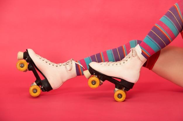 Beine mit hochgestreiften strümpfen und retro-skates auf rosa hintergrund
