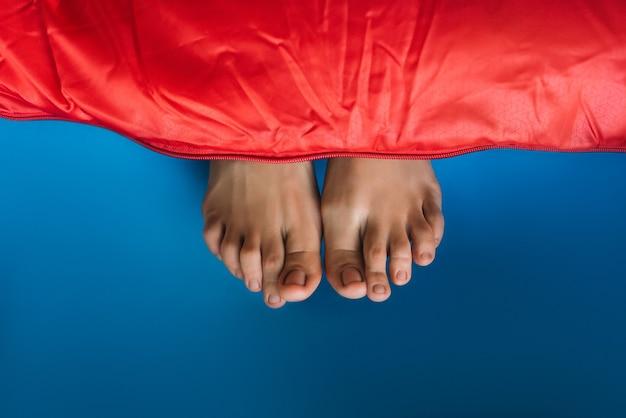 Beine ragen aus dem schlafsack. die beine einer frau ragen aus einem roten schlafsack heraus. beine ragen unter der roten decke hervor. beine unter der decke. ein tourist im schlafsack. platz kopieren