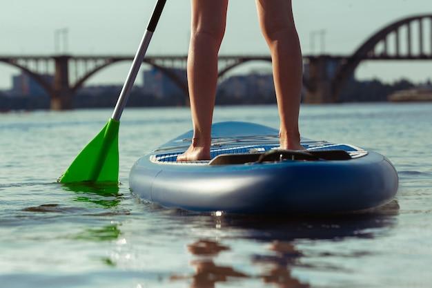 Beine schließen. junge attraktive frau, die auf paddelbrett, sup steht.