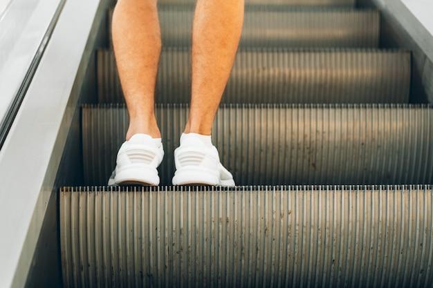 Beine stehen auf der rolltreppe eines einkaufszentrums