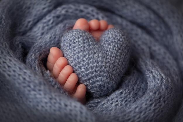 Beine und zehen eines neugeborenen in einer weichen grauen decke mit herz