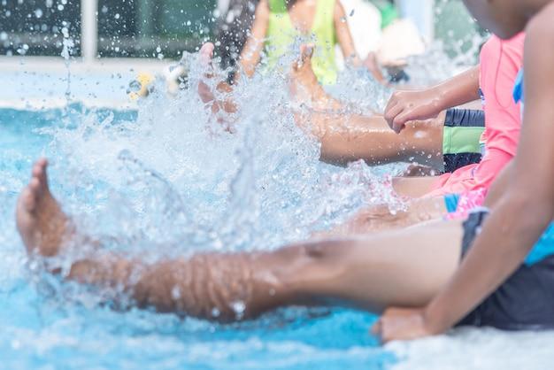 Beinschuß des kindes an der swimmingpoolklasse, die lernt zu schwimmen