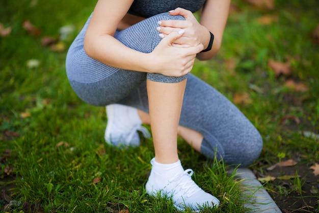 Beinverletzung. schöne frau, die schmerz im knie glaubt