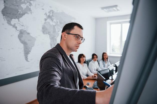 Beispiel auf dem whiteboard zeigen. gruppe von personen an der geschäftskonferenz im modernen klassenzimmer tagsüber