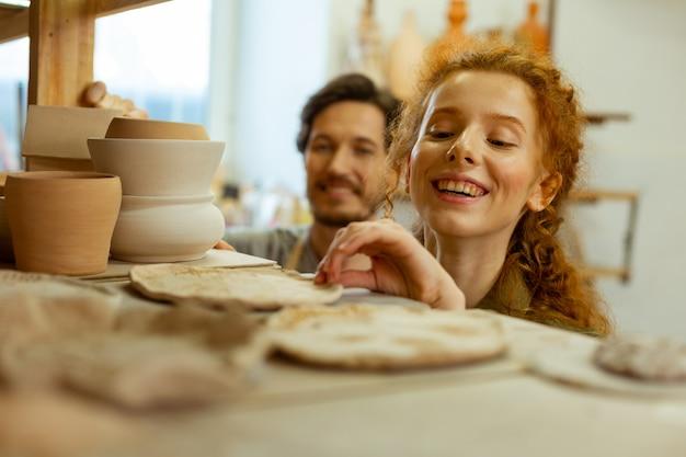 Beispiele prüfen. lachendes angenehmes mädchen, das sich für ungewöhnliche tonstücke interessiert, während es in der werkstatt bleibt
