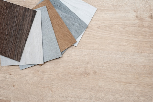 Beispielkatalog von luxus-vinyl-bodenfliesen mit neuem innendesign für ein haus oder einen boden auf einem hellen holztisch.