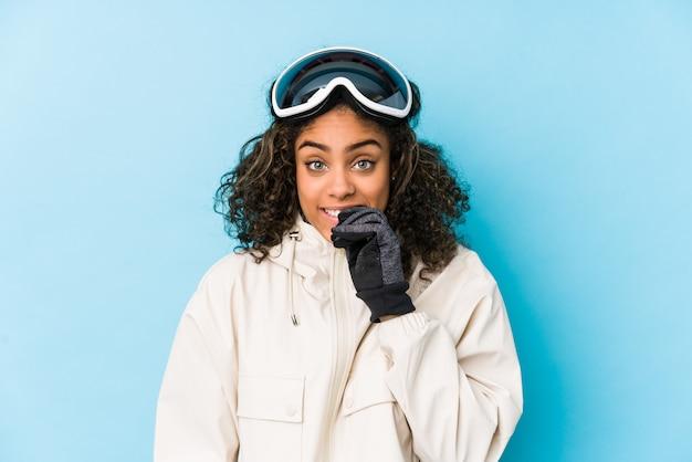 Beißende fingernägel der jungen afroamerikaner-skifahrerfrau, nervös und sehr besorgt.