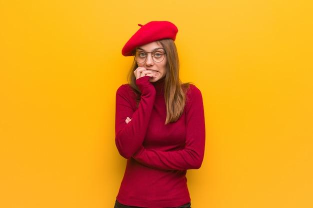 Beißende nägel der jungen französischen künstlerfrau, nervös und sehr besorgt