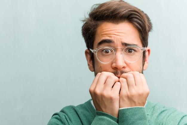Beißende nägel der jungen hübschen unternehmermann-gesichtsnahaufnahme, nervös und sehr besorgt und für die zukunft erschrocken