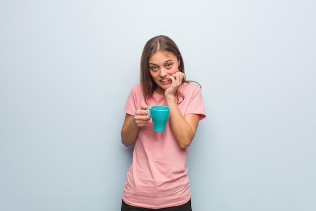 Beißende nägel der jungen recht kaukasischen frau, nervös und sehr besorgt. sie hält eine tasse.