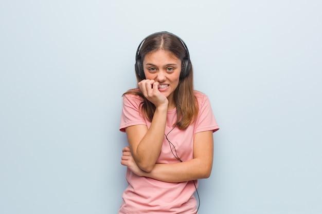 Beißende nägel der jungen recht kaukasischen frau, nervös und sehr besorgt. sie hört musik mit kopfhörern.