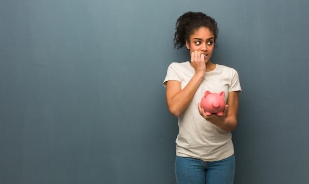 Beißende nägel der jungen schwarzen frau, nervös und sehr besorgt. sie hält ein sparschwein.