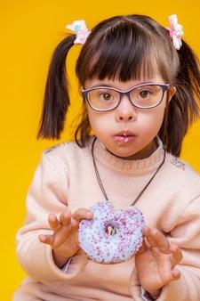 Beißender blauer donut. überraschtes entzückendes kleines kind, das frischen donut zeigt, während sie es schmeckt