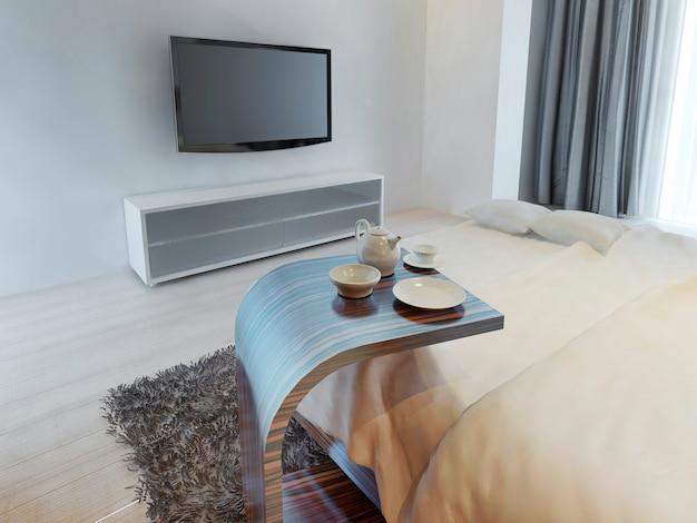 Beistellter couchtisch neben dem bett im zeitgenössischen stil mit kaffeeservice. schlafzimmer mit tv-konsole in weißer farbe. 3d-rendering.