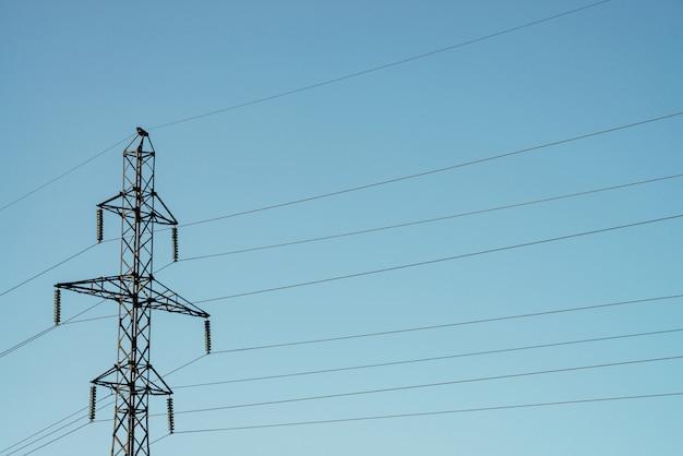 Beiträge mit drähten der hochspannung auf blauem himmel im sonnenlicht.