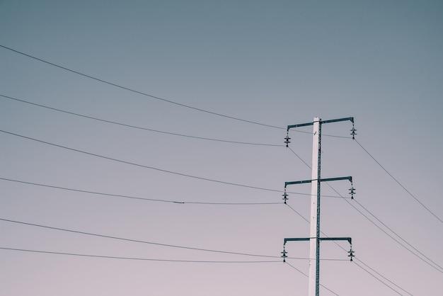 Beiträge mit drähten der hochspannung auf hintergrund des himmels im sonnenlicht. monochromes hintergrundbild vieler drähte im himmel mit kopierraum.