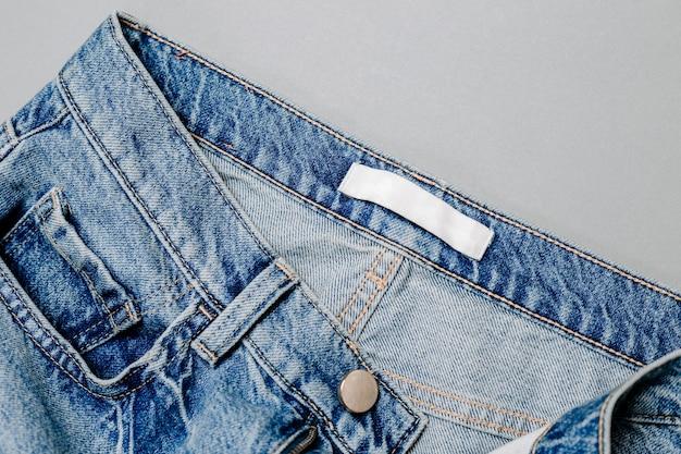 Bekleidungsetikett in jeans auf grauem hintergrund. attrappe, lehrmodell, simulation