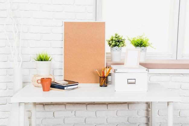 Bekorken sie brett mit büroartikel und stoffkästen auf tabelle