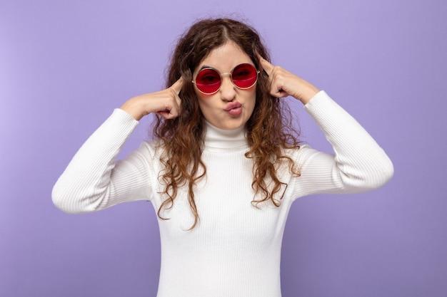 Belästigte junge schöne frau in weißem rollkragenpullover mit roter brille, die ihre schläfen berührt und einen schiefen mund auf lila stehend macht