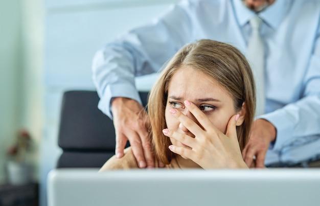 Belästigung mit einem chef, der seine sekretärin, die an seinem arbeitsplatz im büro sitzt, mit dem arm berührt