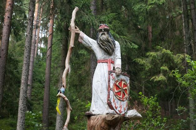 Belarussische nationale holzskulpturen im wald. heidnischer holzgott perun mit stab und schild.