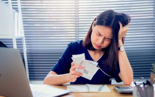 Belastungsgesichts-asiatinhand, die ausgabenrechnung und -berechnung über schuldenrechnungen monatlich am tisch im innenministerium hält.