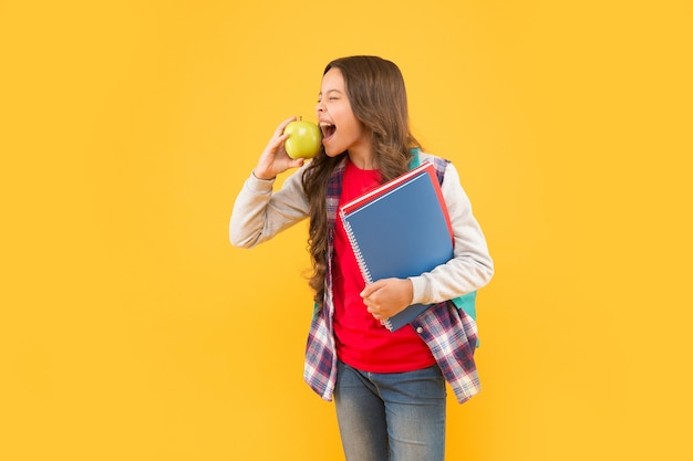 Belebe deine vorstellungskraft. kleines mädchen beißen apfelgelber hintergrund. snack für die schule. gesunde essgewohnheiten. ernährung und gesundheit. fantasie der kindheit. phantasie und fantasie. sie ist eine hastige leserin.