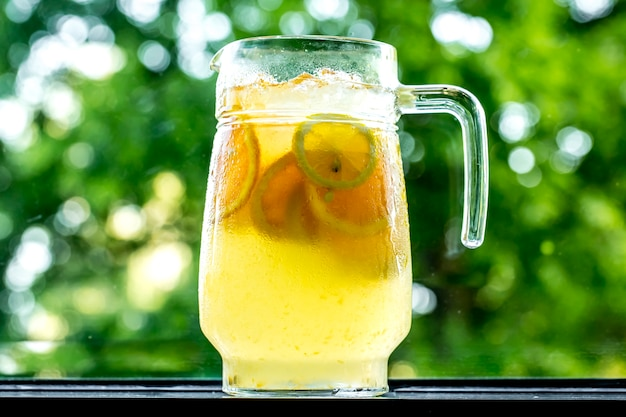 Belebende limonade der vorderansicht im dekanter mit zitrone und orange