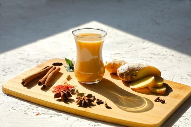 Belebender masala-tee. gesundheitstee mit gewürzen, zutaten an der tafel. in den hellen strahlen der sonne.
