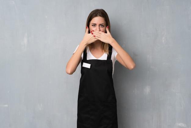 Belegfrauenbedeckungsmund mit den händen für das unpassendes sagen