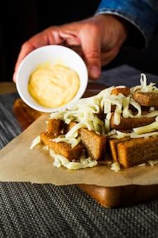 Belegte roggenbrotcroutons besprüht mit geriebenem käse und soße auf einer hölzernen platte