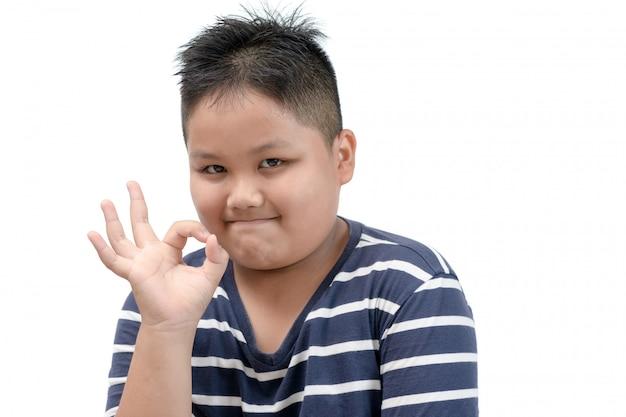 Beleibter fetter junge, der das okayzeichen lokalisiert zeigt