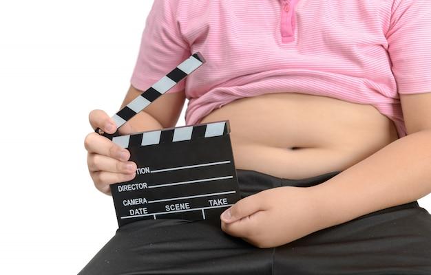 Beleibter fetter junge, der scharnierventilbrett oder schieferfilm hält