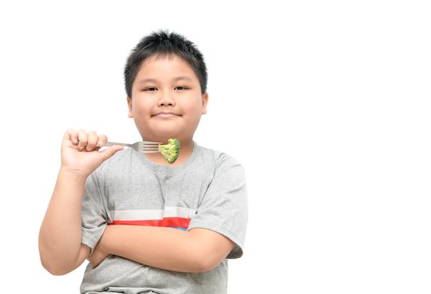 Beleibter fetter junge mit dem brokkoli an hand lokalisiert auf weißem hintergrund, gesundem lebensmittelkonzept und kopie spac