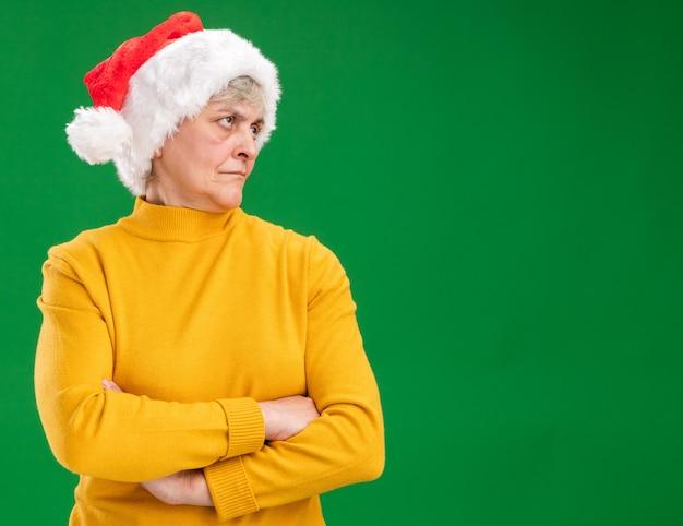 Beleidigte ältere frau mit weihnachtsmütze steht mit verschränkten armen zur seite schauend