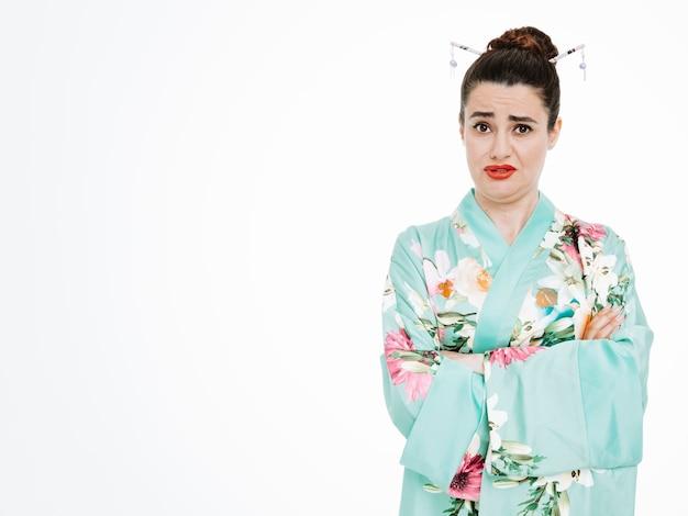 Beleidigte frau im traditionellen japanischen kimono mit traurigem ausdruck mit verschränkten armen auf weiß