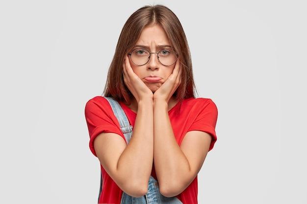 Beleidigte junge süße brünette frau hat unzufriedenen ausdruck missbraucht, spitzt die unterlippe, hält die hände auf den wangen, trägt eine runde brille und ein rotes t-shirt, will nicht arbeiten oder studieren, posiert drinnen