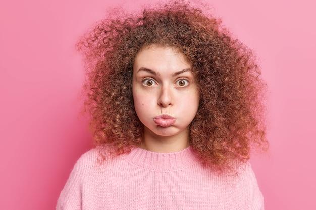 Beleidigte lockige junge europäerin bläst wangen macht grimasse, gekleidet in lässigen pullover hält den atem an und sieht überraschend isoliert über rosa wand aus. gesichtsausdrücke konzept