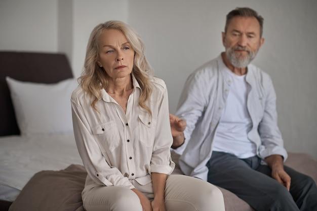 Beleidigte reife frau, die ihren männlichen ehepartner missachtet