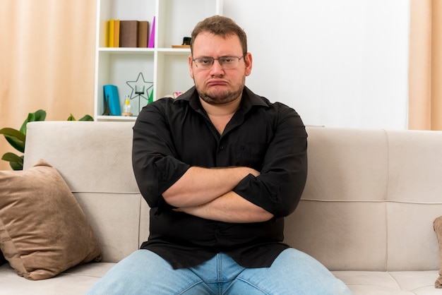 Beleidigter erwachsener slawischer mann in optischer brille sitzt auf sessel mit verschränkten armen im wohnzimmer