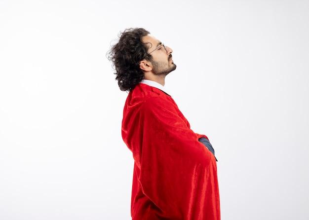Beleidigter junger kaukasischer superheldenmann in optischer brille, der anzug mit rotem mantel trägt, steht seitlich mit verschränkten armen